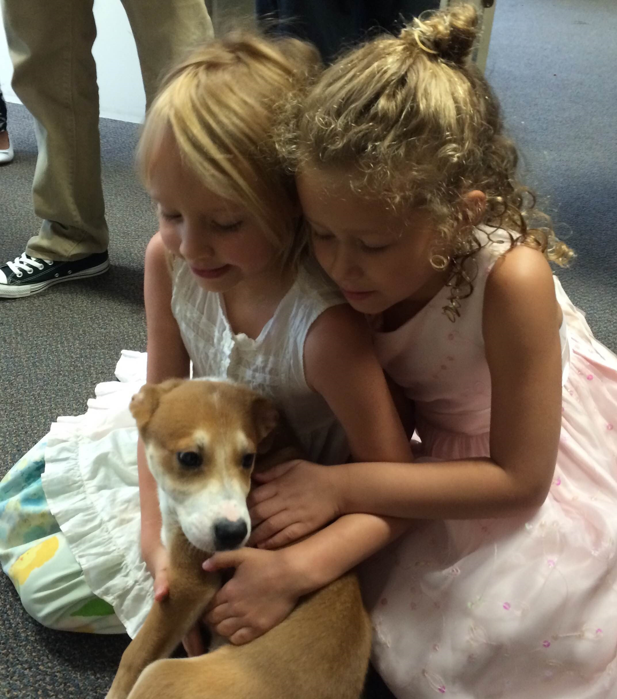 Two girls petting puppy in church entryway