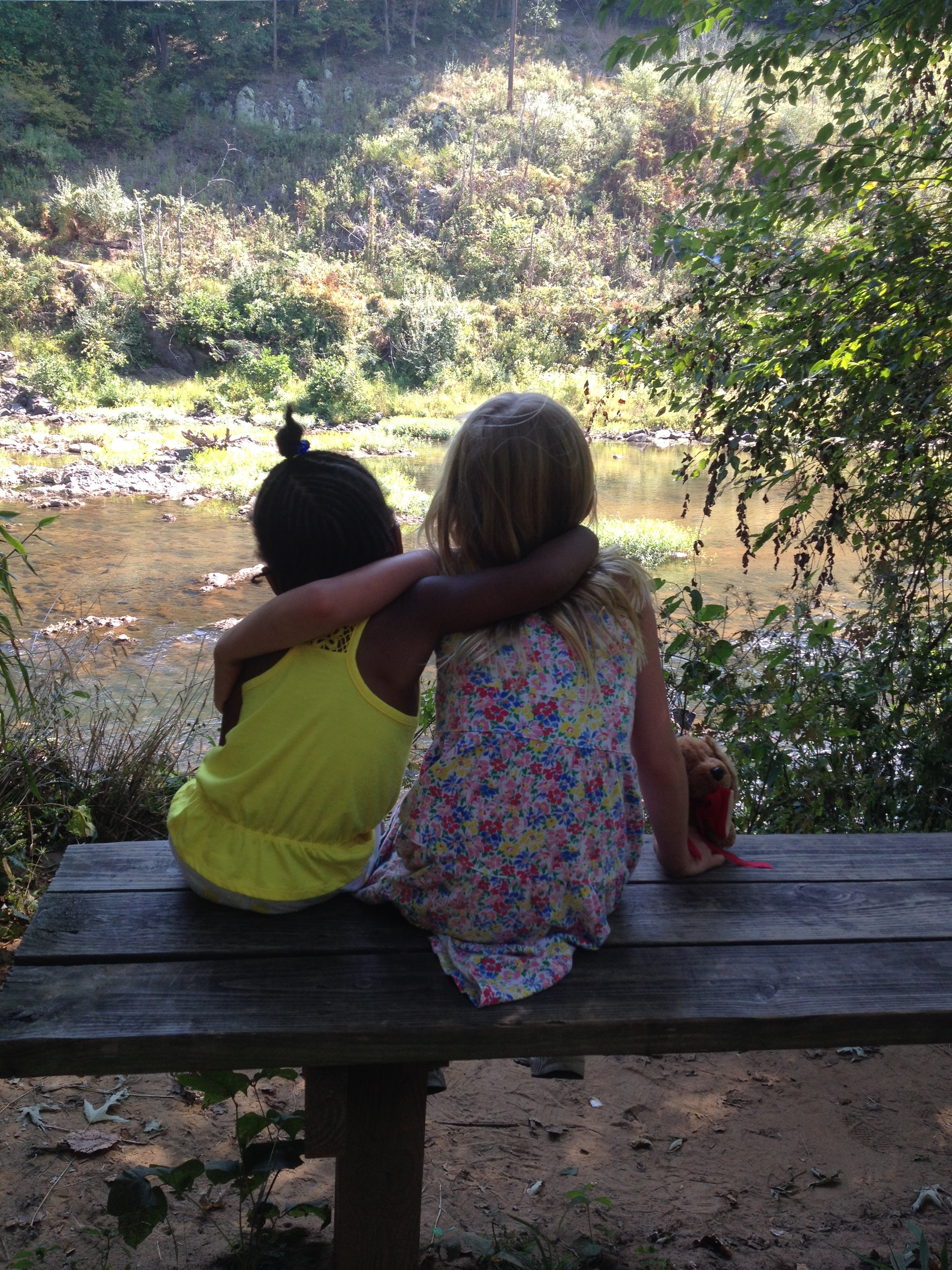 Backs of two girls side by side watching river